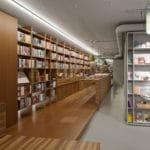 Eingangsbereich mit wildem Nussbaum starkfurnier und roh MDF lackiert mit Verkaufstheke und Bücherregal