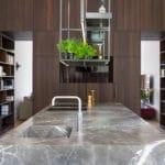 Küchenblock aus FIORE DI BOSCO in Abwicklung mit Küchenrückwand aus Räuchereiche und beleuchtetem Stahlregal über der Küche mit Quooker Wasserhahn