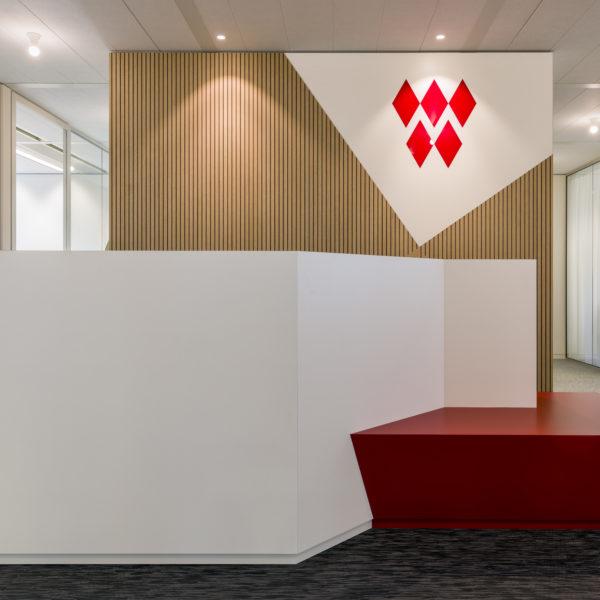 Maverick Amsterdam Meetingpiont mit Holzrückwand und Plexiglaslogo