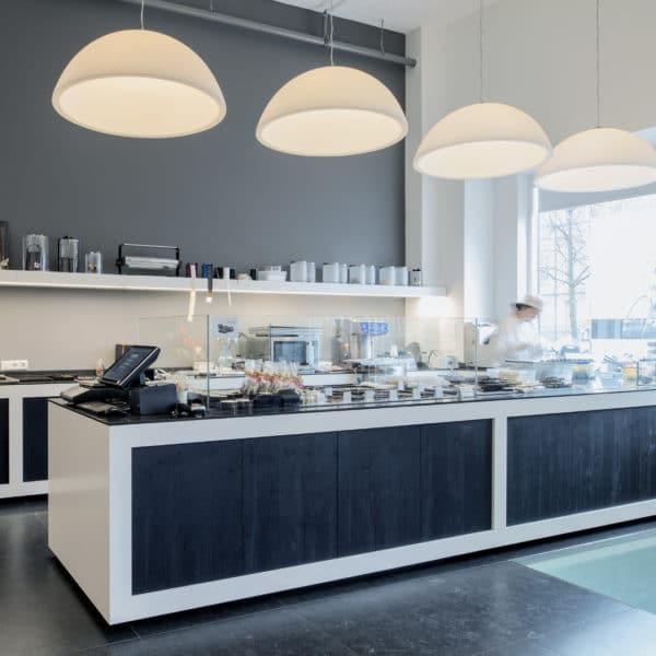 Patisserie Theke für Ladenverkauf und die Herstellung von Schokolade und Schokoladenkreationen mit Glasaufsatz Aus HPL mit Holzoptik schwarz